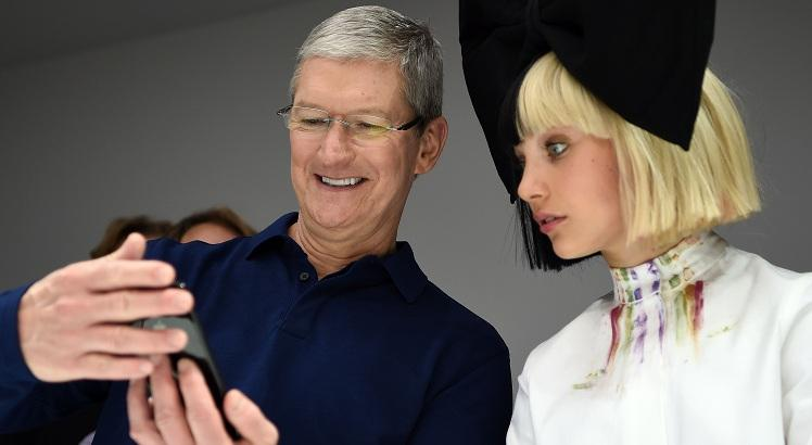 TOPSHOT - Apple CEO Tim Cook (L) shows dancer Maddie Ziegler (R) a new iPhone during a product demonstration at Bill Graham Civic Auditorium in San Francisco, California on September 07, 2016.   / AFP / Josh Edelson